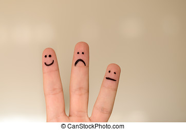 Three different emoticons hand drawn on fingers with a black...