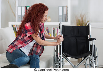 disabled trying to sit down on wheelchair
