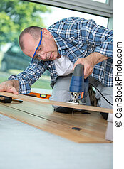 carpenter cutting laminated planks for layered parquet using...