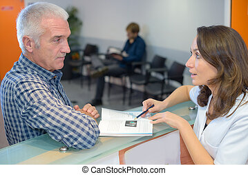 Man looking at booklet at hospital reception