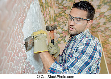 Man chipping tiles off a wall