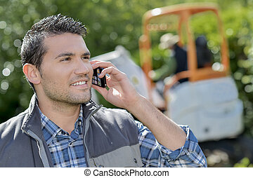 Young and smiling labourer on the phone