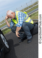 discouraged retired man unable to change car tyre