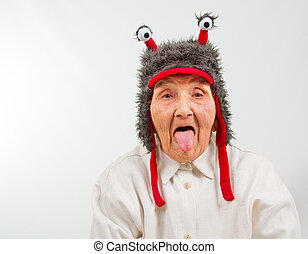 grandma in funny hat puts her tongue out - very old lady in...