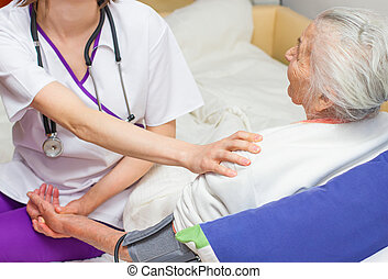 young nurse caregiving an old lady lying in bed - Young...