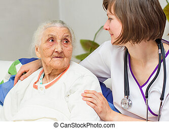 young nurse caregiving an old lady lying in bed - Happy...