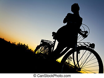 Love to ride my bike - Girl on old bicycle at sunset