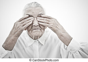 grandma is blind - very old woman masking her eyes with her...