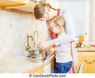 Teamwork in the kitchen - Little girl and mother cooking...