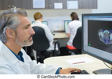 Senior medic studying image on screen