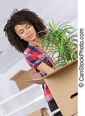 woman carrying boxes and plant at house