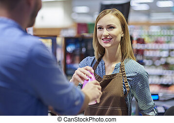 Woman working in gorcery checkout