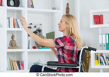 Disabled woman reaching book from shelf