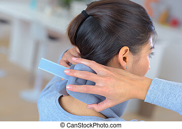 woman putting on cervical collar to herself