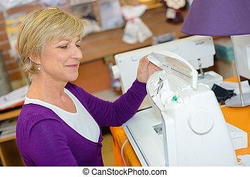 Mature lady using sewing machine