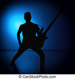 silhouette guitarists of a rock band with guitar on blue...