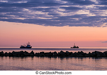 Ships and sunset on shore of the Baltic Sea.