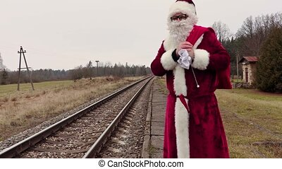 Santa Claus with gift bag on platform near railway