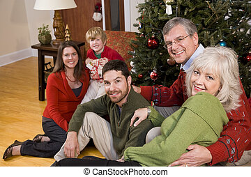 Family holiday gathering by Christmas tree - Three...
