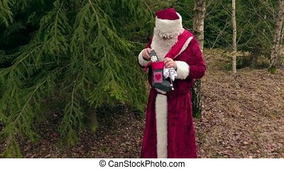 Santa Claus with gifts near spruce in forest