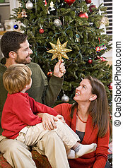 Family sitting by Christmas tree, dad holding star - Family...