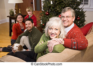 Senior couple with family by Christmas tree - three...