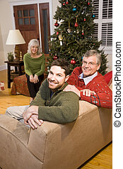 Mid-adult man and senior parents by Christmas tree - Happy...