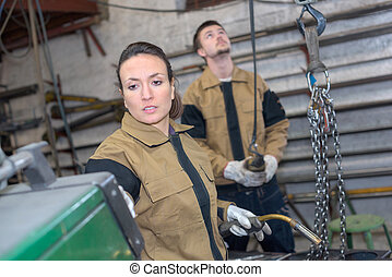female welder and coleague at the factory