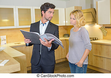 Couple in kitchen looking at catalogue