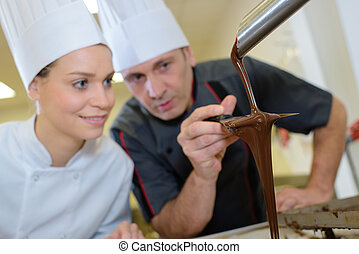 team of pastry cooks smiling a commercial kitchen