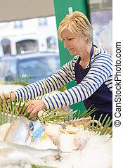 Female fishmonger tending stall