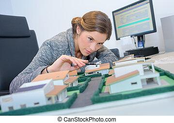 Woman looking at model housing development