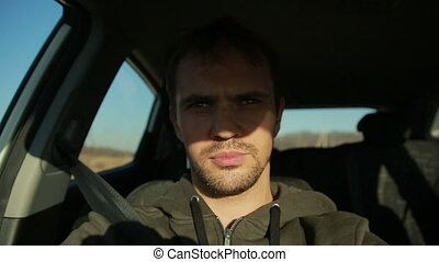 the young man behind the wheel of a car