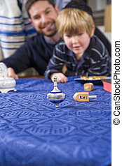 Boy with father spinning dreidel - Boy with father and...