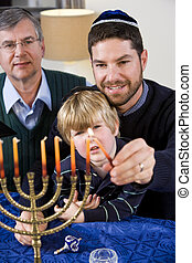 Jewish family lighting Chanukah menorah - Three generation...