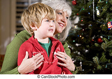 Boy sitting on grandmother's lap by Christmas tree - Four...