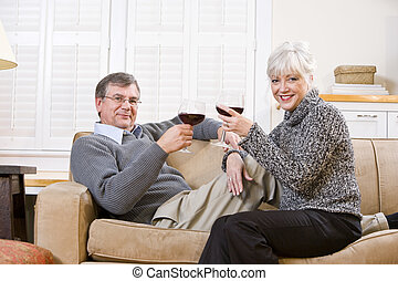 Senior couple relaxing together on couch with wine