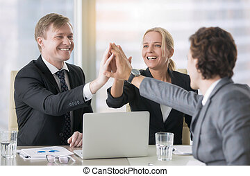 A group of business leaders giving high five - A group of...
