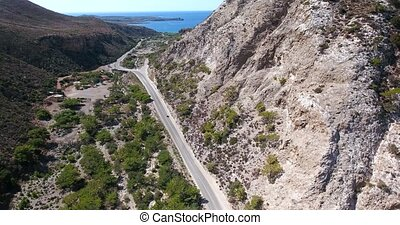 road through mountains to sea at crete Greece - road through...
