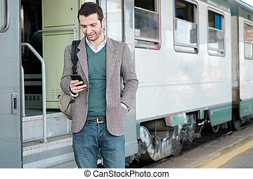 Standing man calling on the phone waiting for the train in a...