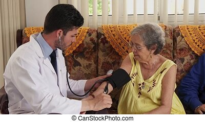 Doctor Working In Hospital And Measuring Blood Pressure Of...