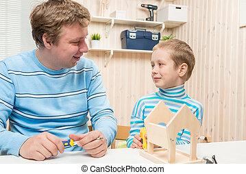 father and son preschooler build a wooden bird feeder