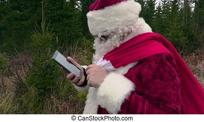 Santa Claus using tablet and laughing