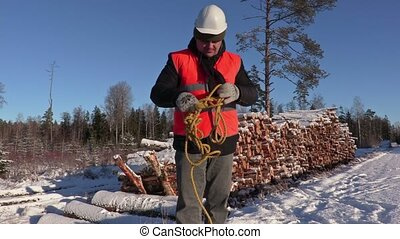 Lumberjack try collect rope near pile of logs in winter