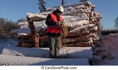 Lumberjack try collect rope near pile of snow covered logs...