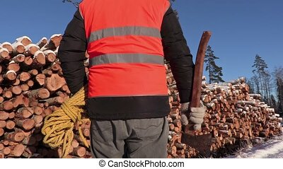 Lumberjack with rope and ax  near pile of logs
