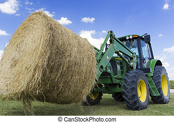 Tractor moving hay bale