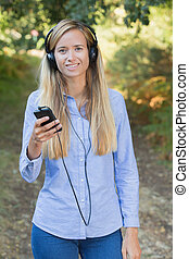 woman listening to music with headphones at the park