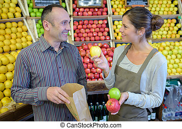 Shop assistant showing man three varieties of apple