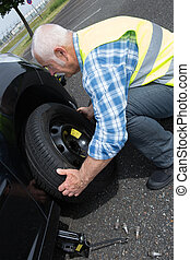 aged man changing leaking tire on the verge